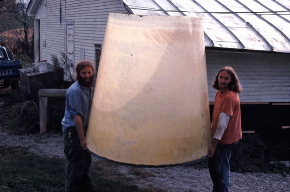 Dr. Barry Costa-Pierce (right) and friend carrying the solar algae pond to set it up.